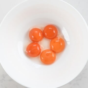 five egg yolks in a bowl