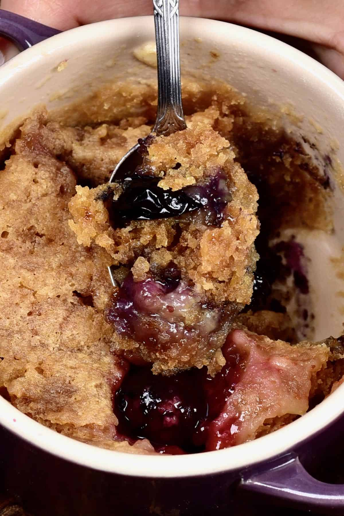 A close up of berry mug cake in a spoon