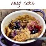 A ramekin with berry mug cake and a spoon