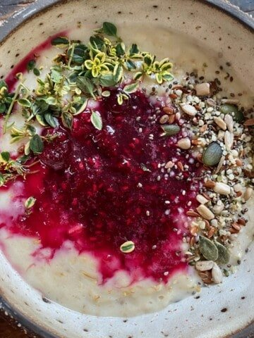 A bowl with berry oatmeal topped with seeds and herbs