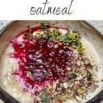 Berry oatmeal in a bowl topped with seeds and herbs