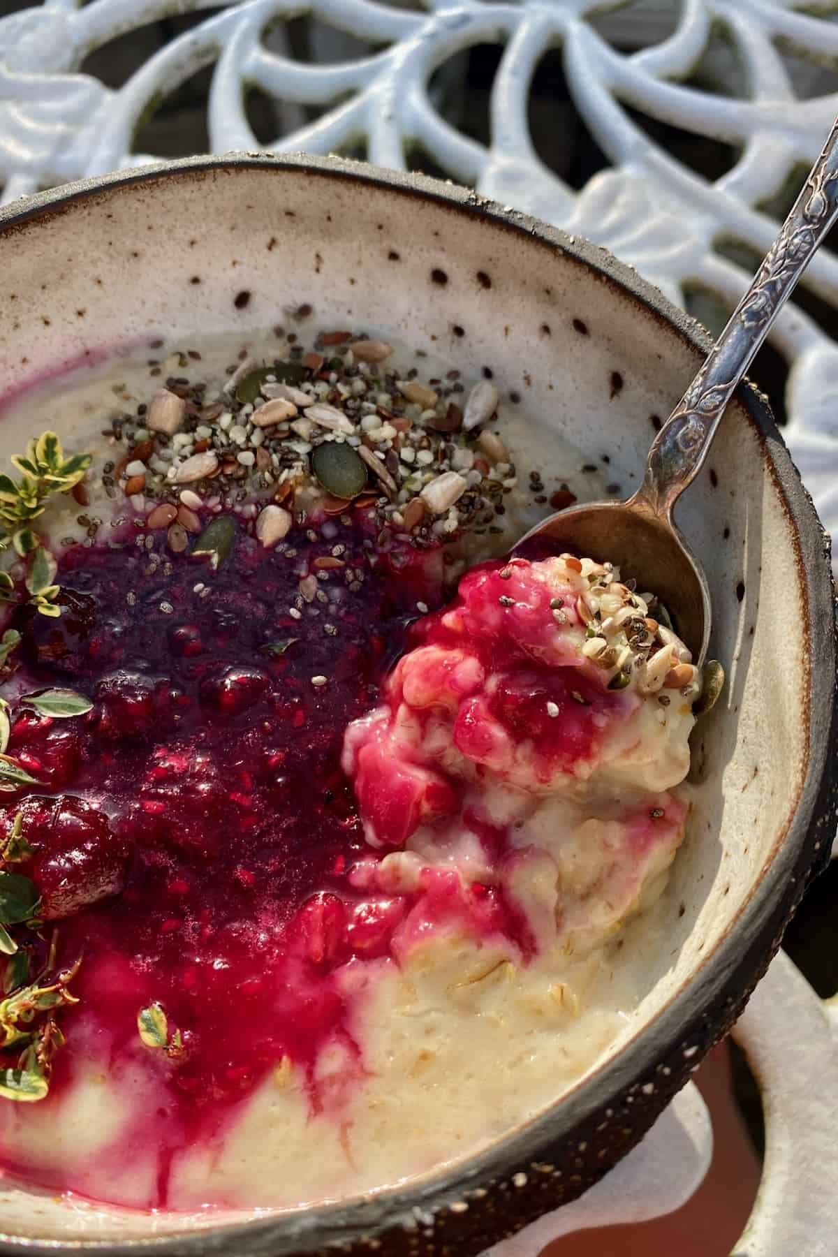 A bowl with a spoon and berry oatmeal topped with seeds and herbs