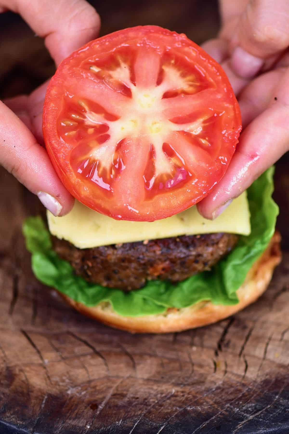 Adding a tomato slice over a burger