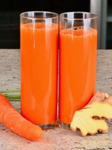 Two glasses with carrot ginger juice and a carrot and ginger next to them