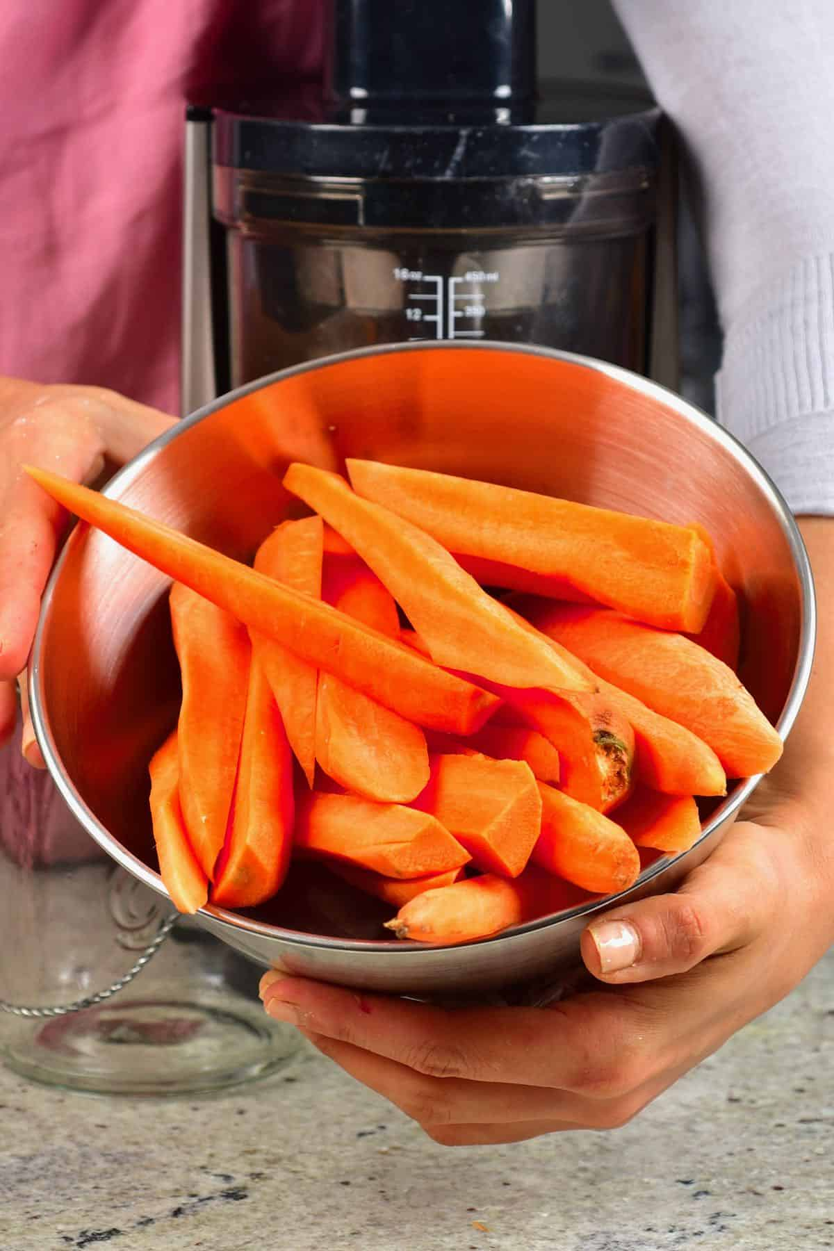Sliced carrots in a bowl in front of a juicer
