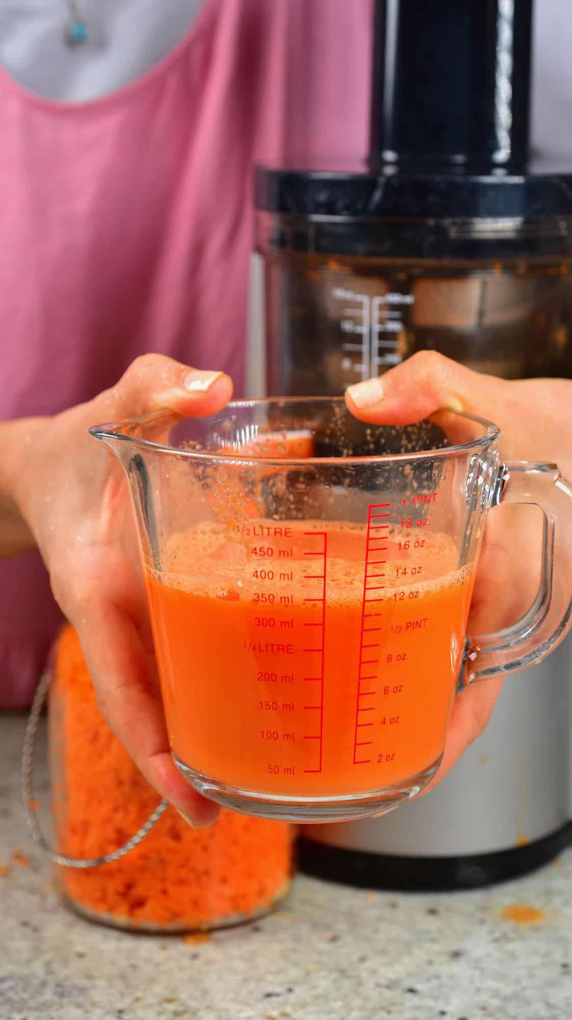 Carrot juice in a measuring cup with a juicer behind it