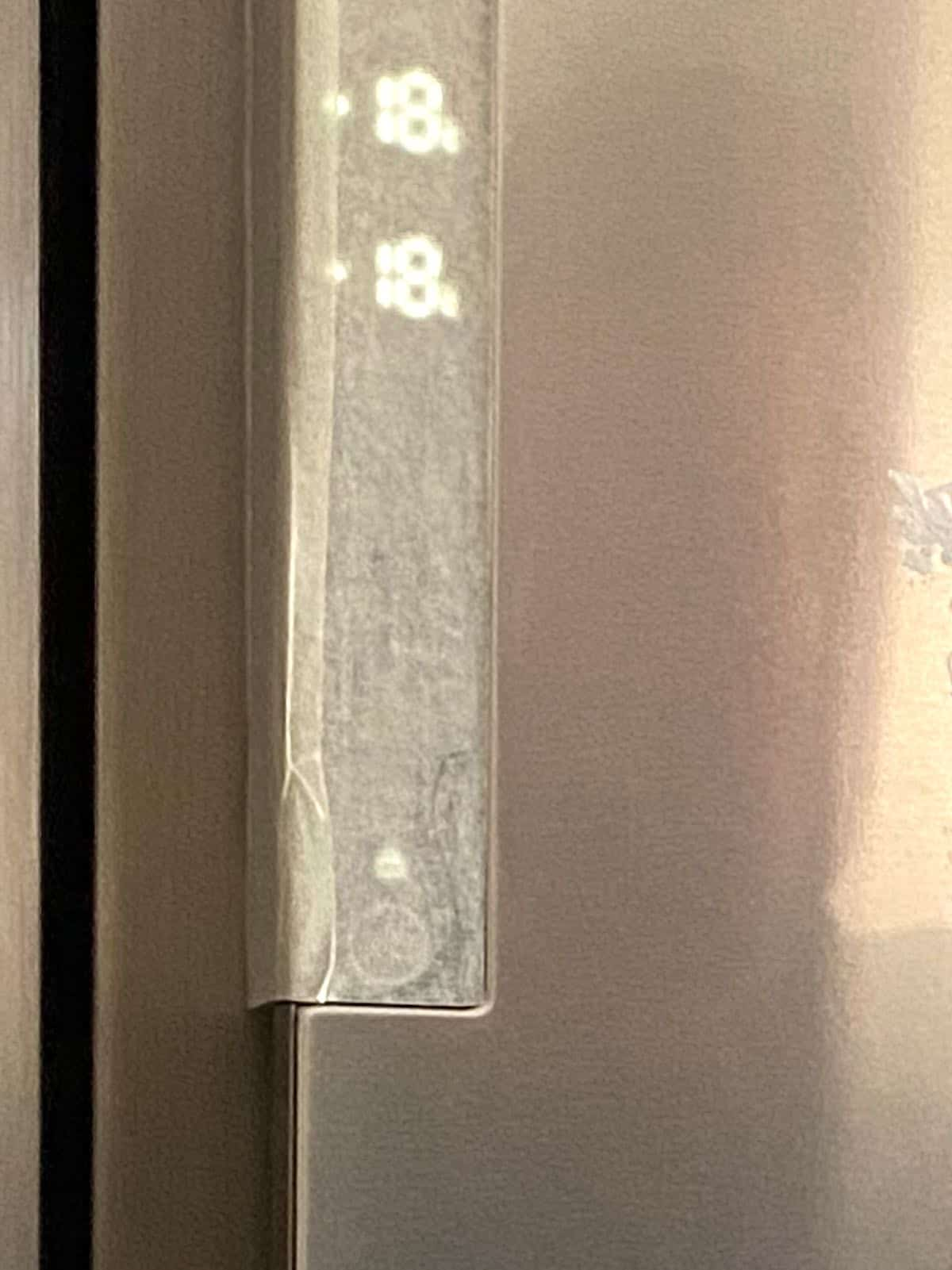 Areas of the a fridge covered with protective tape