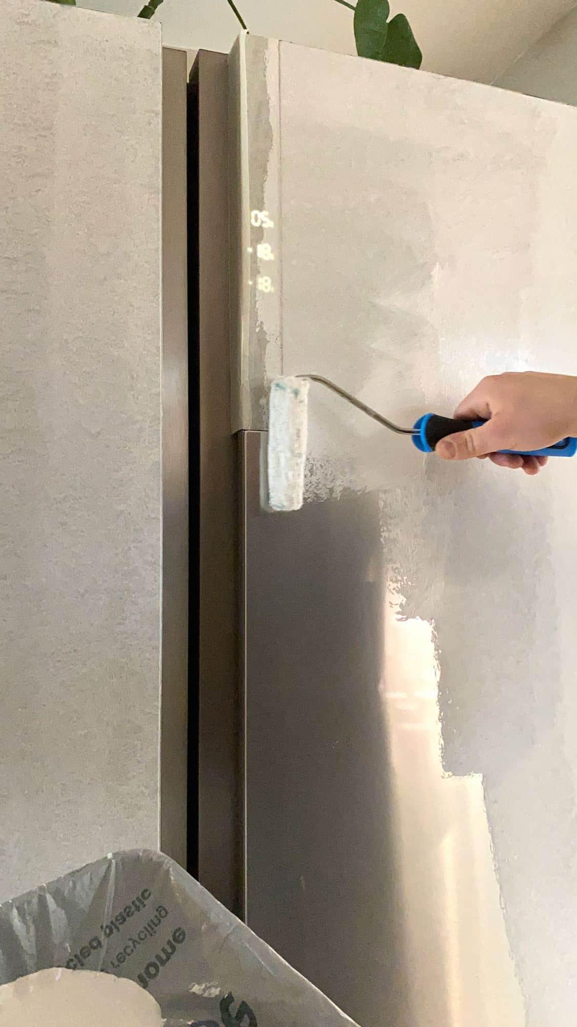 Applying primer paint on fridge surface