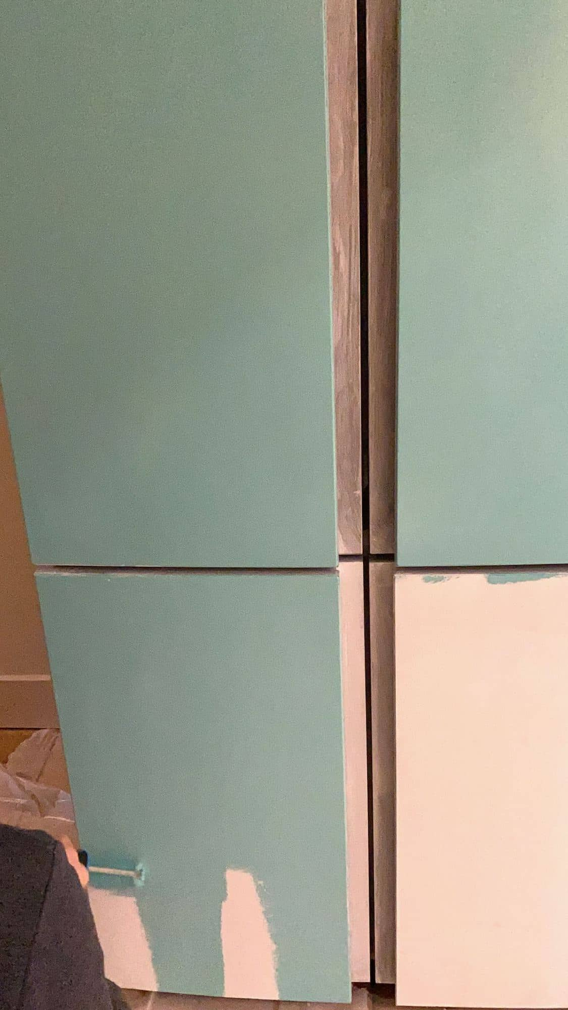 Three of the four doors of a fridge freezer newly painted with turquoise paint