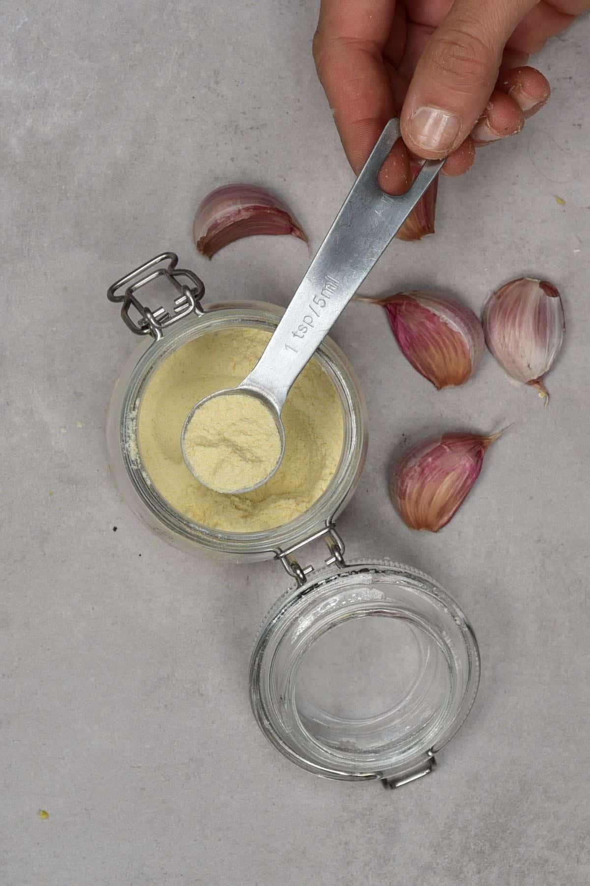 A teaspoon with garlic powder over a jar