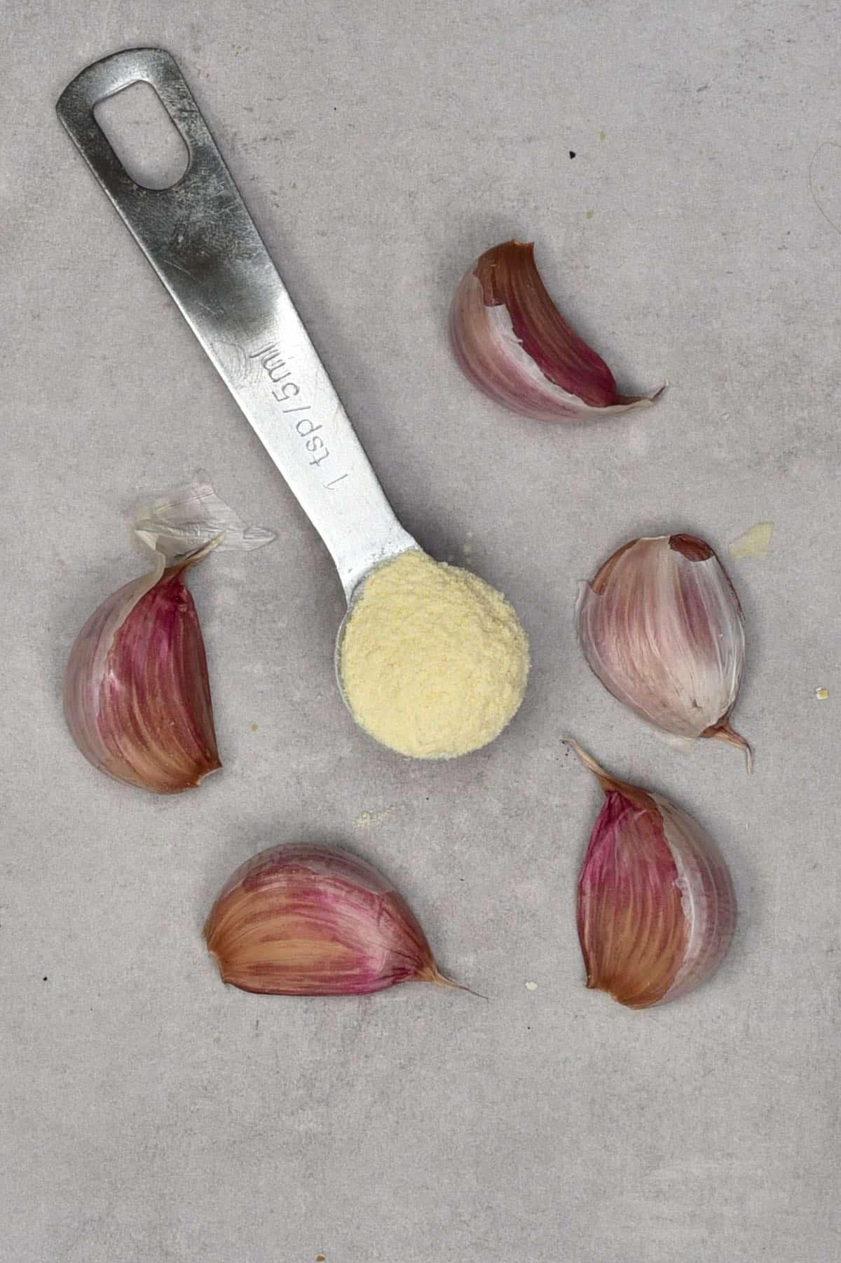 Garlic powder in a teaspoon with five garlic cloves around it