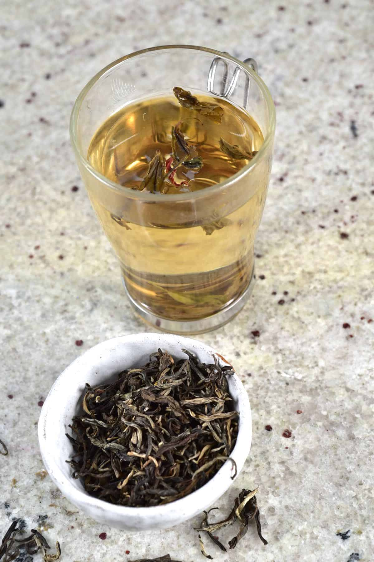 Tea in a glass with hot water and some loose tea leaves in a small bowl