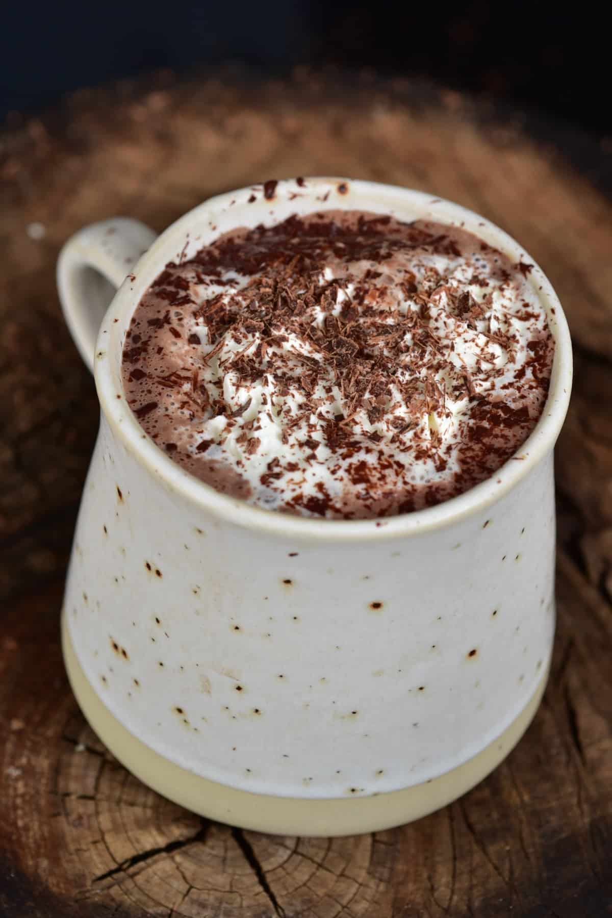 Hot chocolate topped with whipped cream and chocolate shavings in a cup