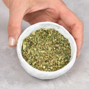 A hand holding a small bowl with Italian seasoning