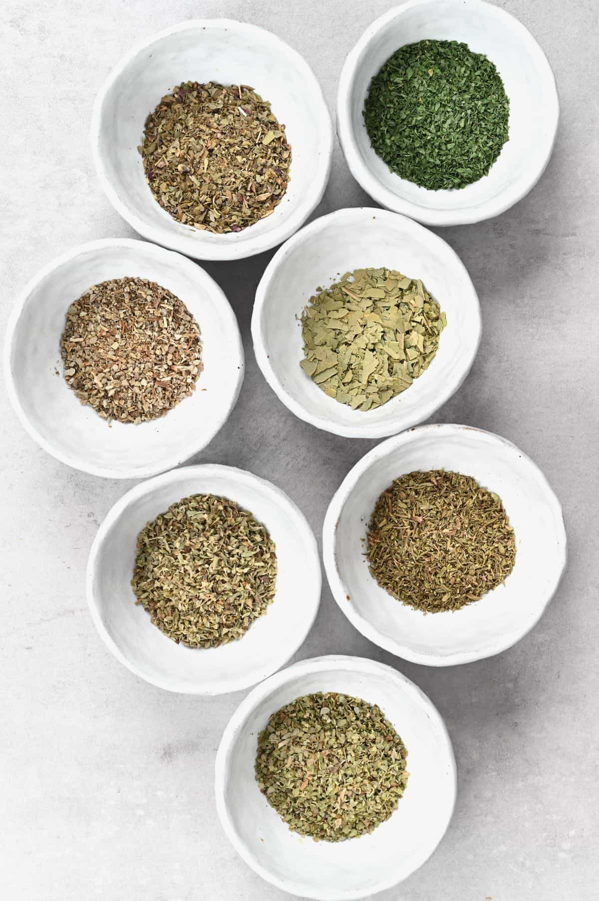 Seven little bowls with different dried herbs