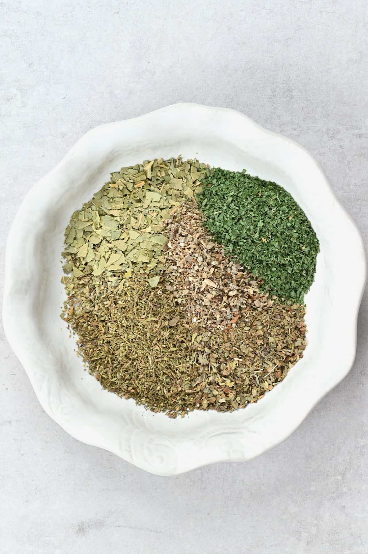 A bowl with seven different dried herbs, not mixed
