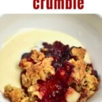 A serving of berry crumble with some custard
