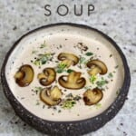 A bowl of mushroom soup topped with mushrooms and thyme