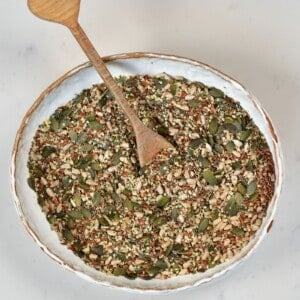 Omega seed mix in a bowl with a wooden spoon