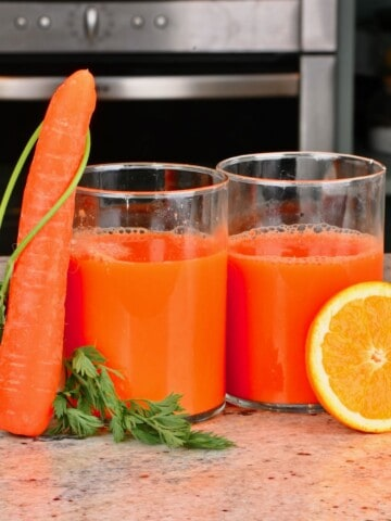 Two glasses of orange carrot juice with a carrot and a slice of orange next to them