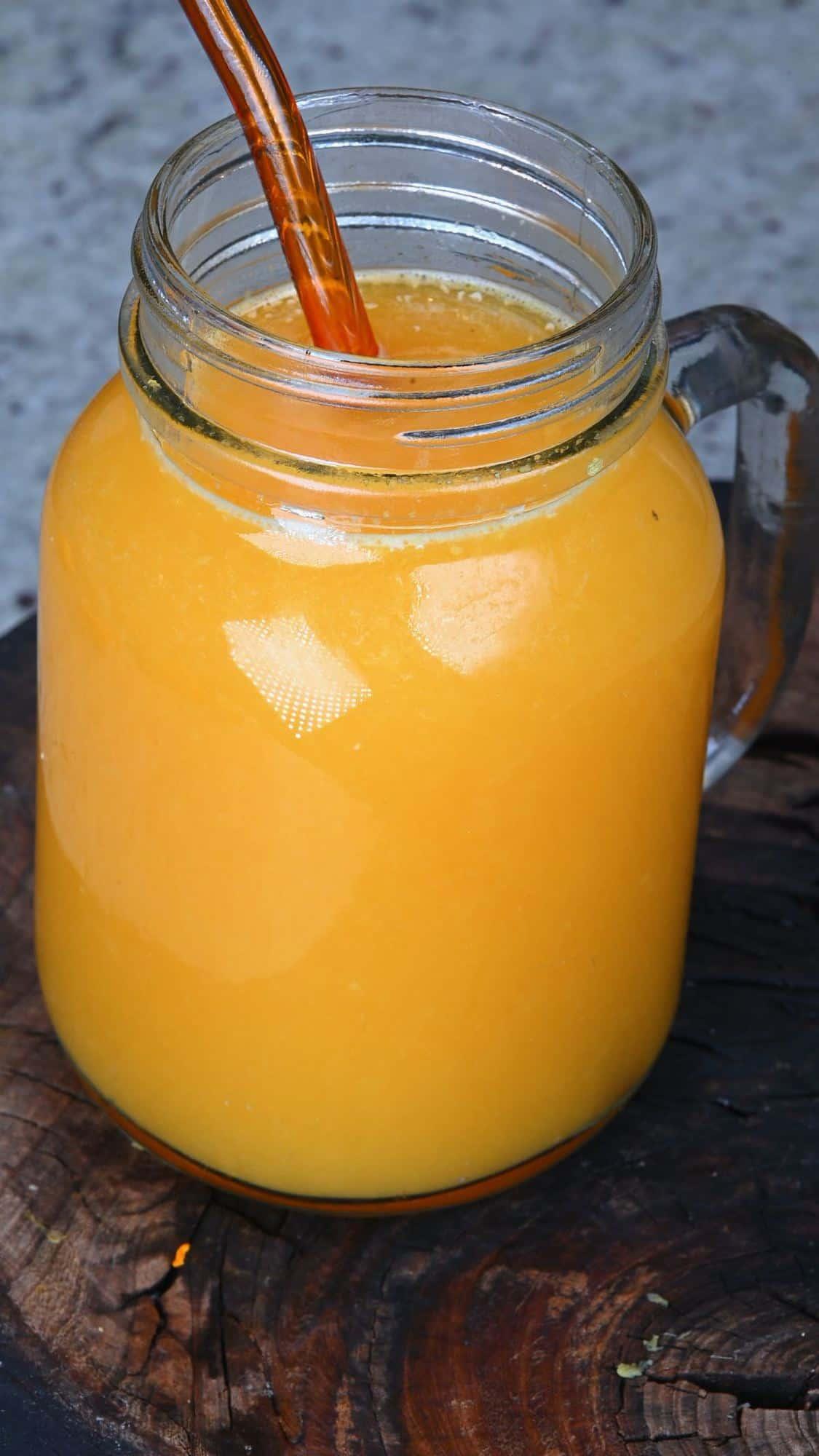 A mason jar with orange juice and a glass straw