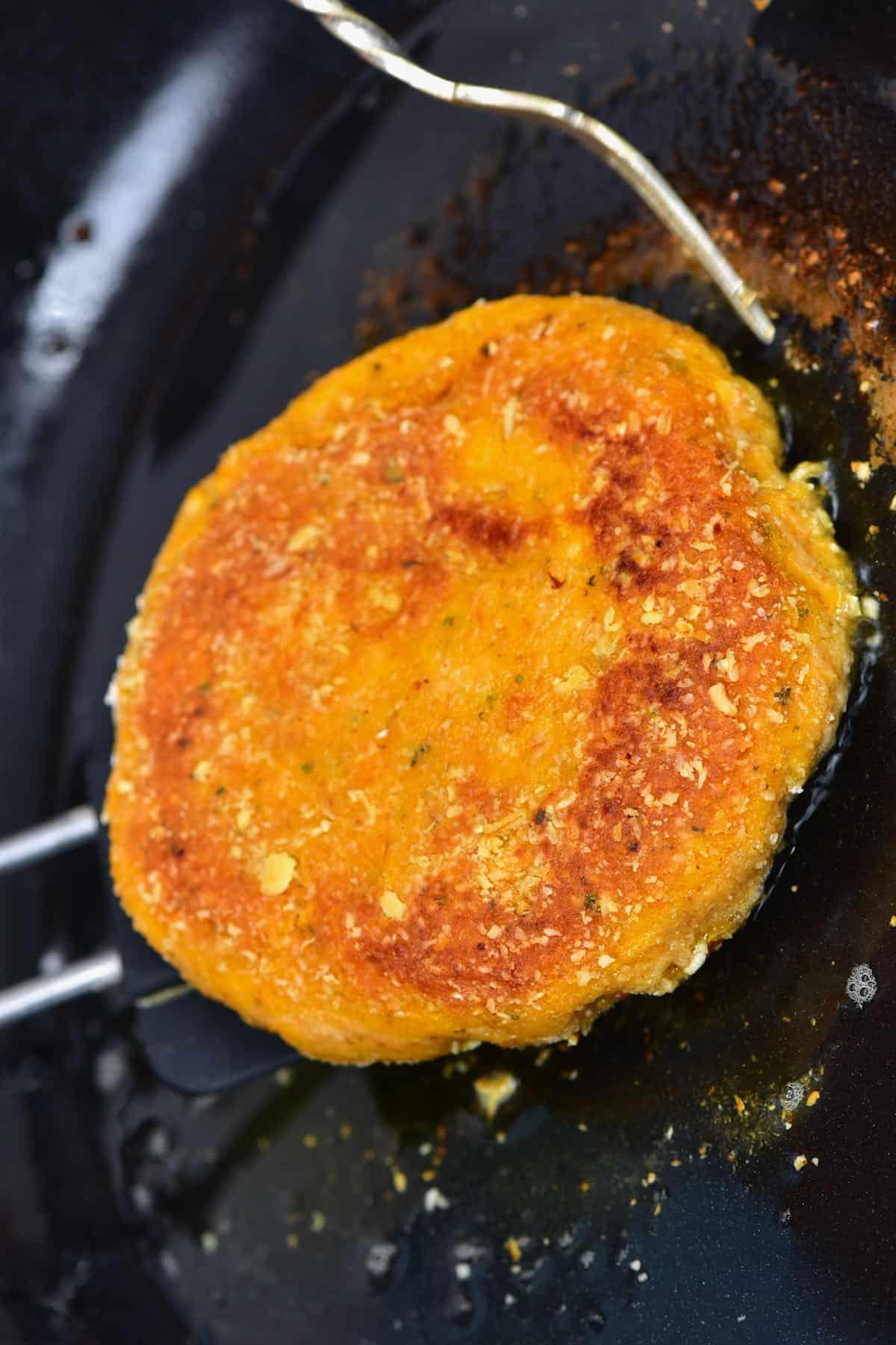 Frying a pumpkin burger patty in a pan
