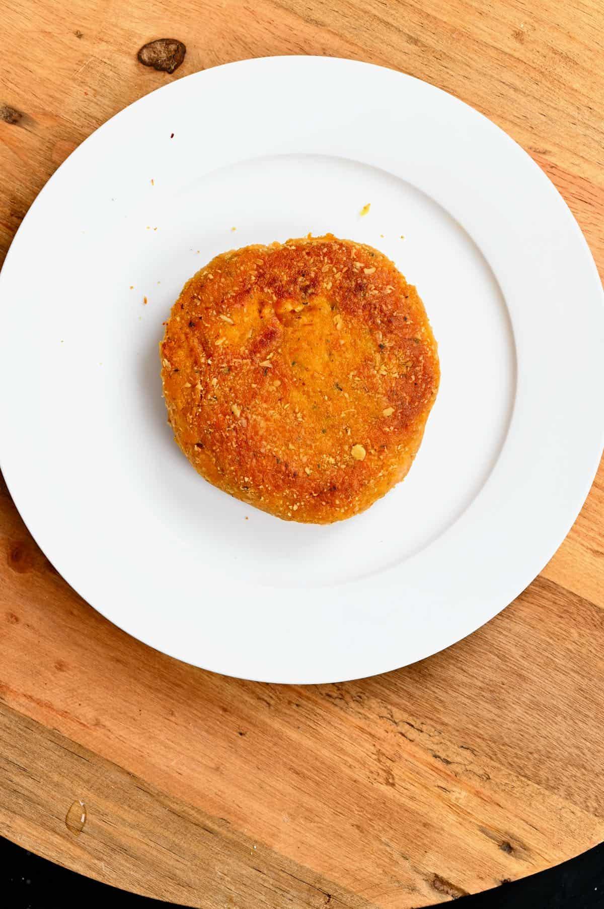 A pumpkin burger patty in a white plate