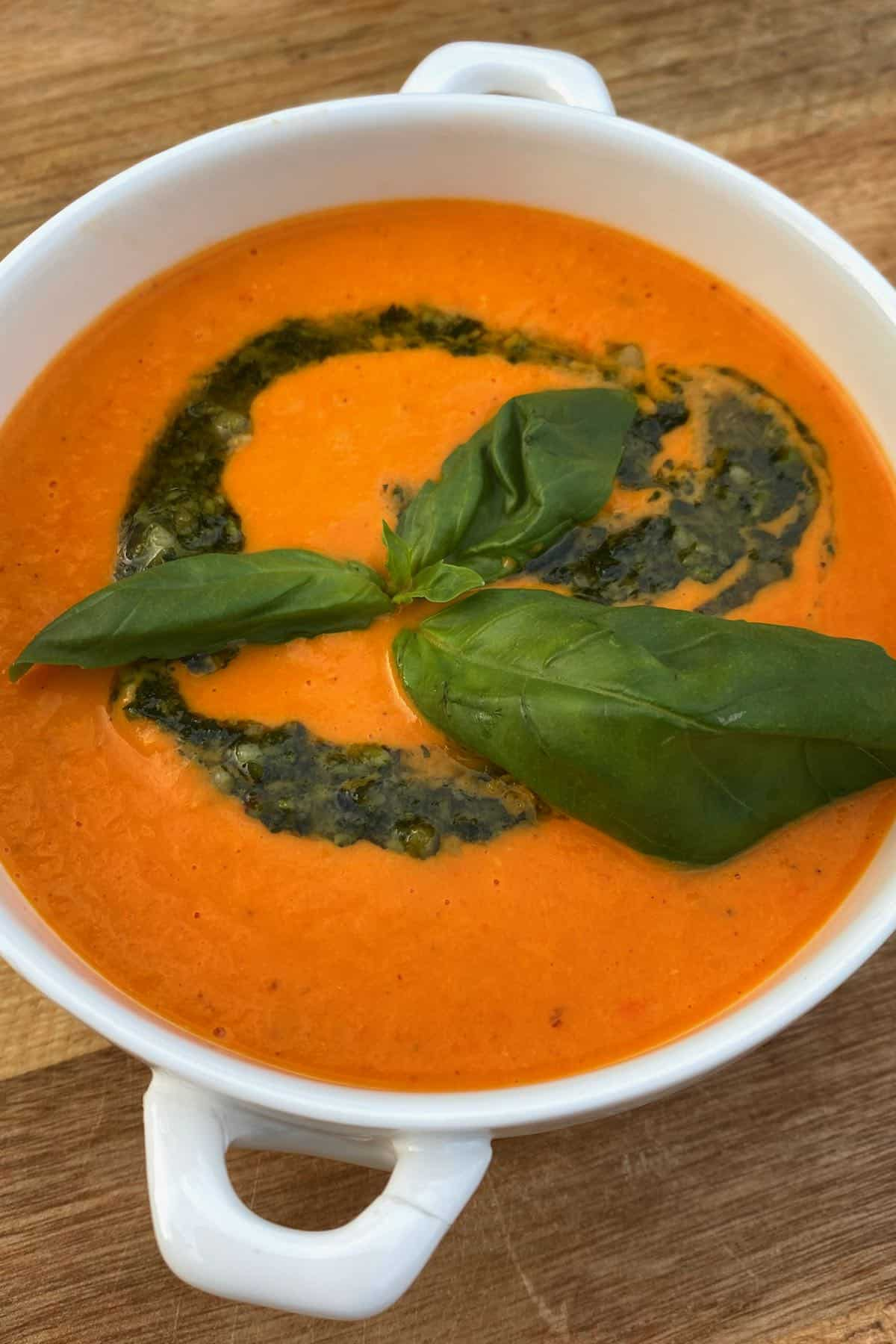A bowl with tomato soup and pesto drizzle