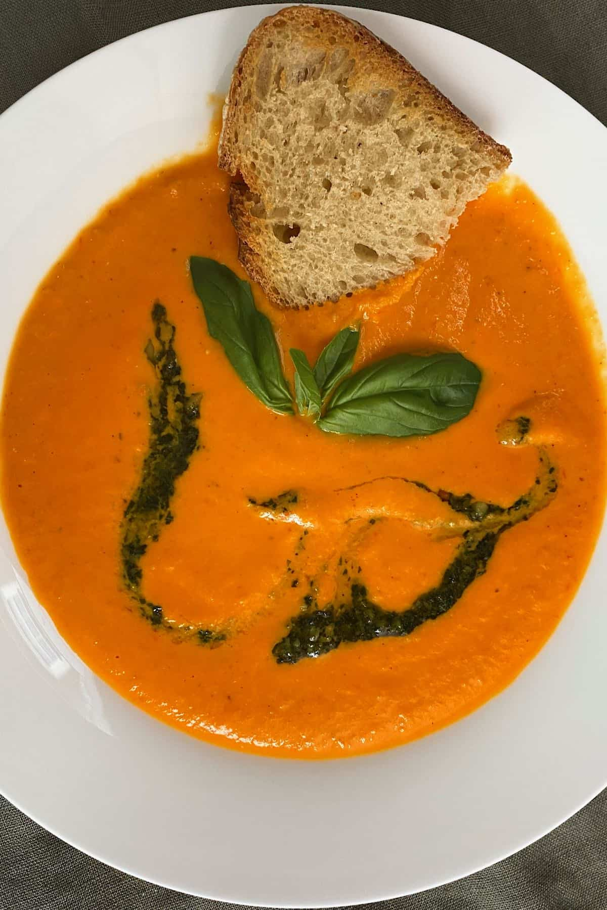 A bowl with tomato soup and a toasted piece of bread being dipping into it