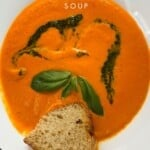 A bowl of tomato soup topped with basil leaves and a piece of bread