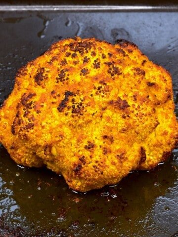 Baked cauliflower head in a baking tray