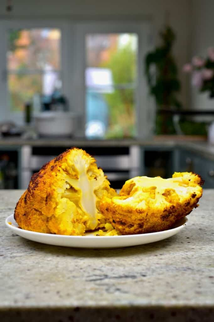 A baked turmeric covered cauliflower head cut in two