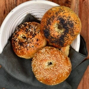Three bagels over a grey towel in a white bowl