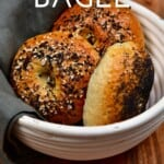 three bagels in a white bowl with a kitchen towel hanging off