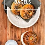 Two bagels in a white bowl and one bagel with cream cheese