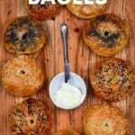 Nine homemade bagels with different toppings arranged in a circle with a small bowl of cream cheese in the middle