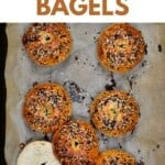 Five whole bagels and one cut in half in a baking tray