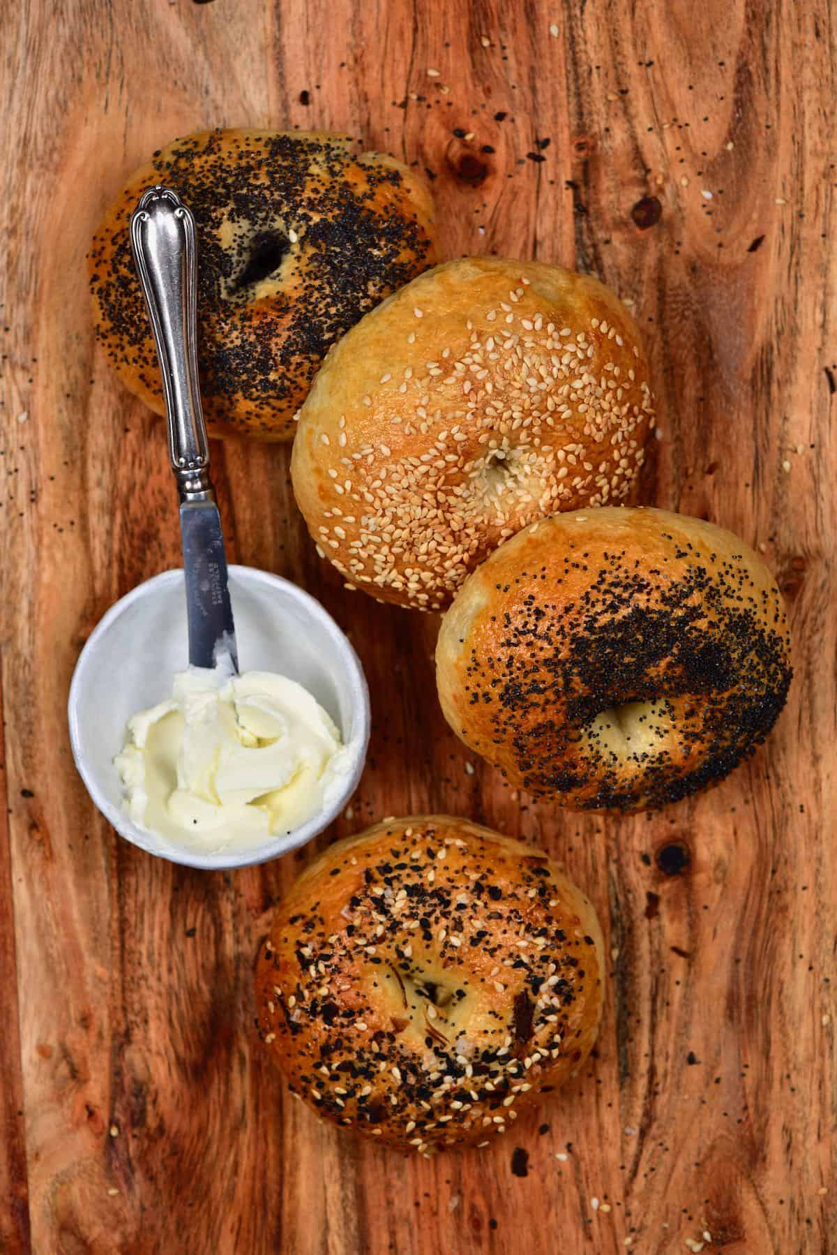 Four bagels and a bowl with cream cheese and knife