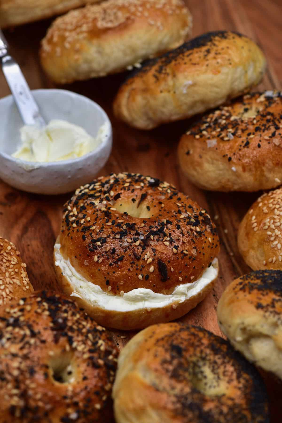 Bagel with cream cheese with other whole bagels around it