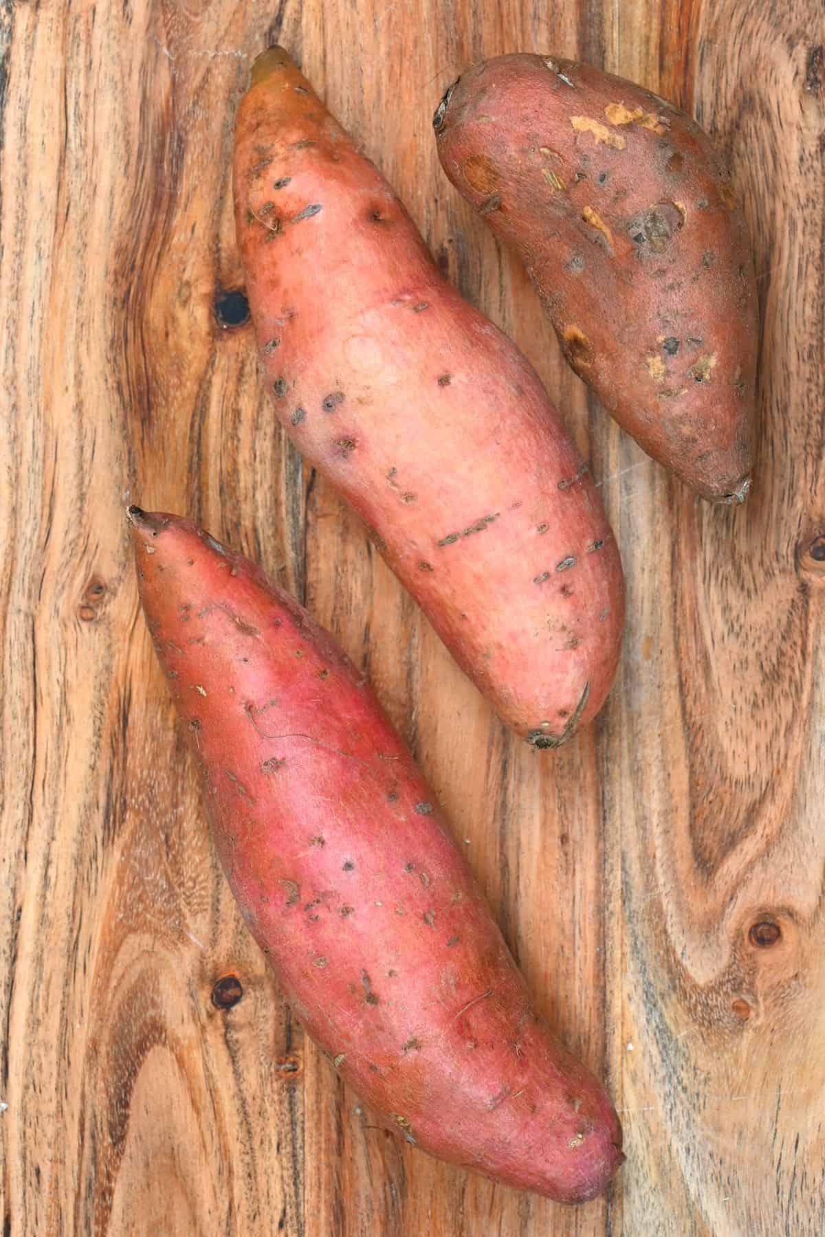 Three sweet potatoes on a wooden board
