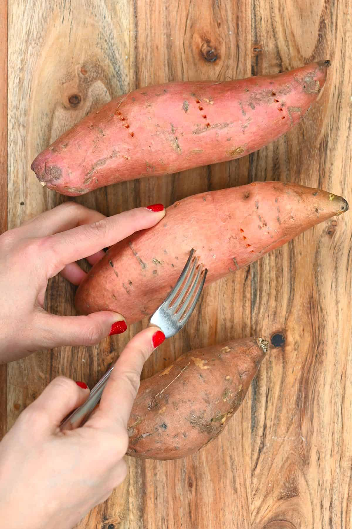 Poking sweet potatoes with a fork