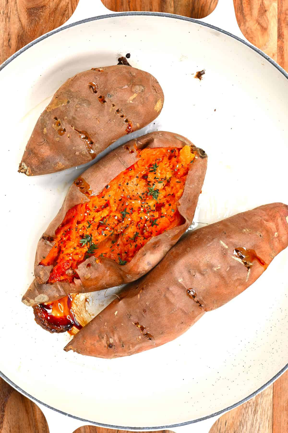Three baked sweet potatoes with one of them open
