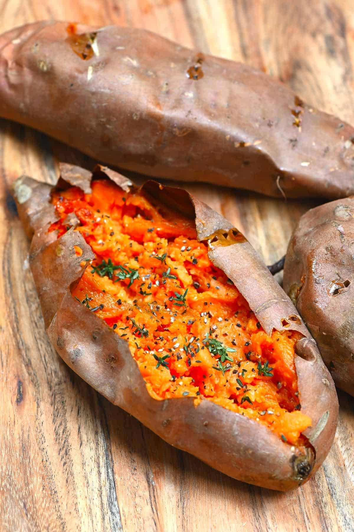Baked sweet potatoes with one of them open and topped with thyme