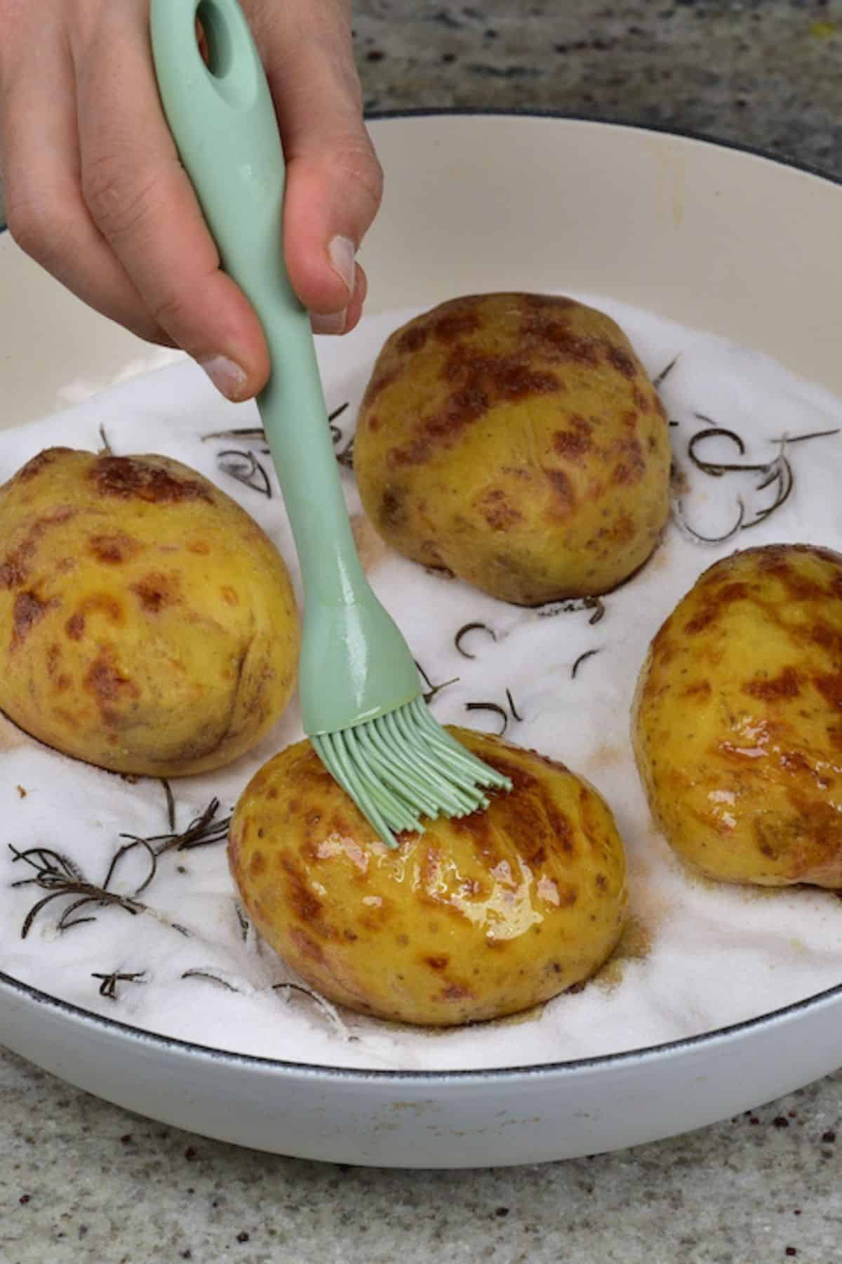 Brushing baked potato with oil