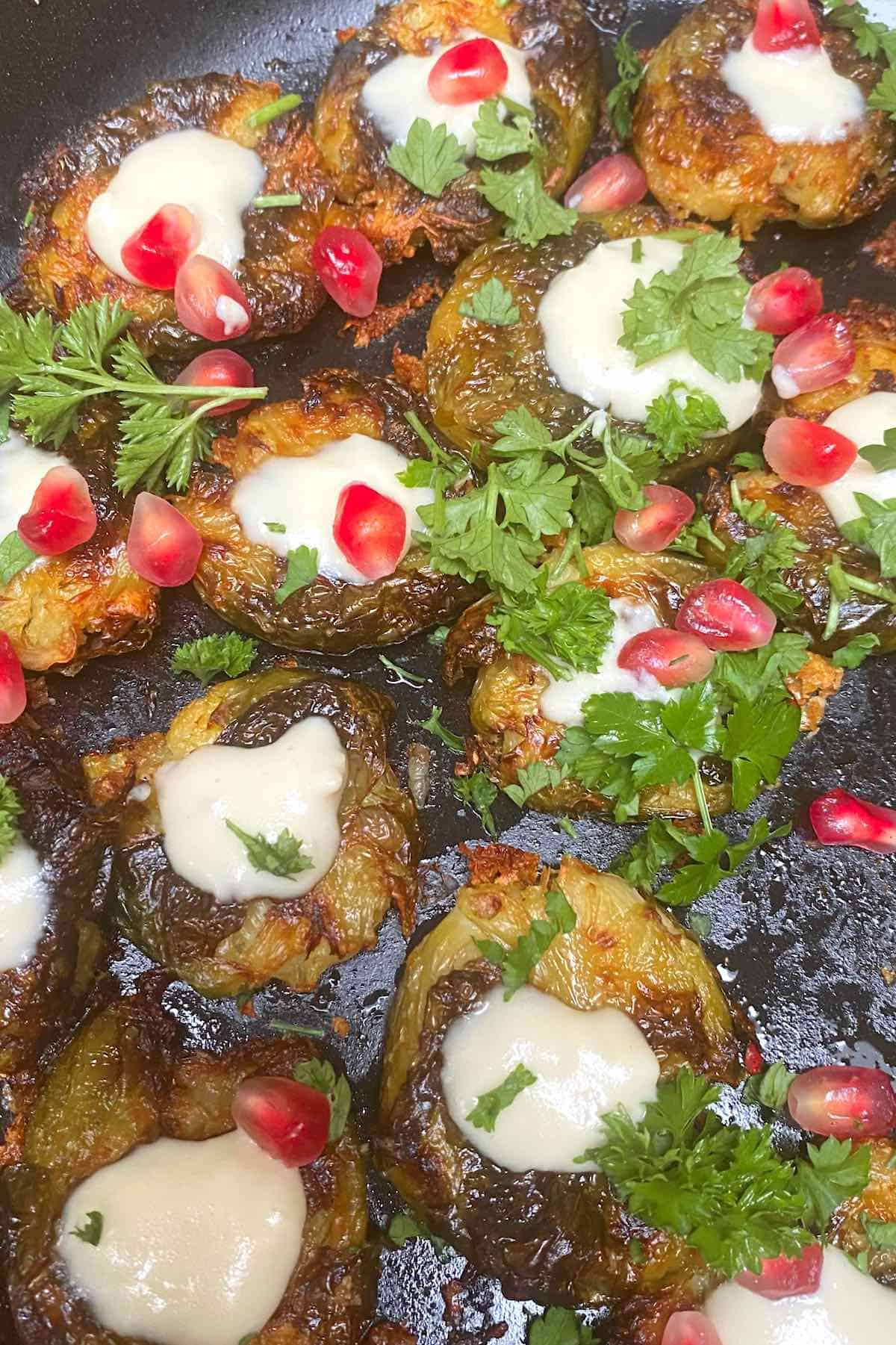 Close up of Roasted Brussels sprouts toped with sauce and pomegranate seeds
