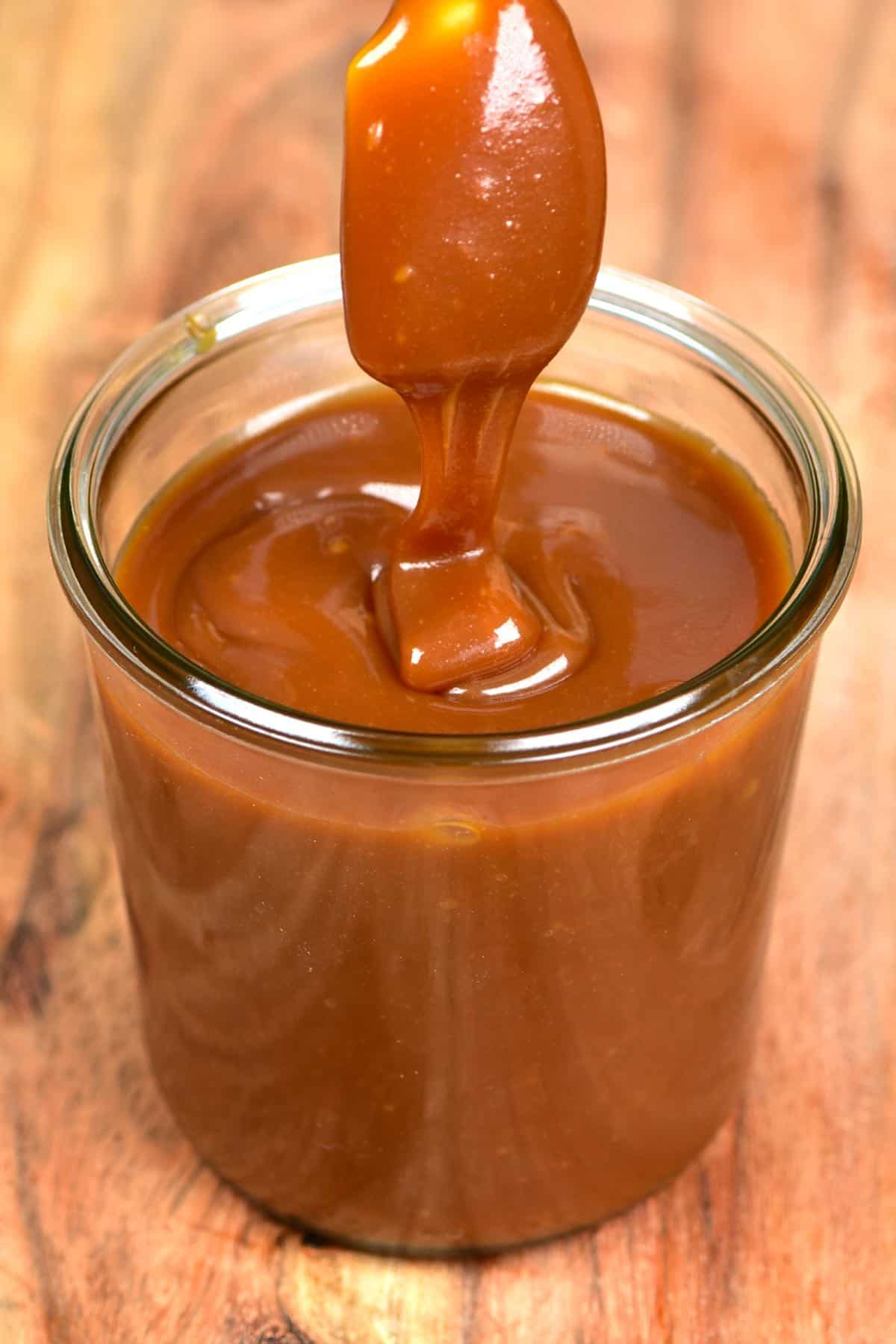 Dipping a spoon into a jar with homemade caramel