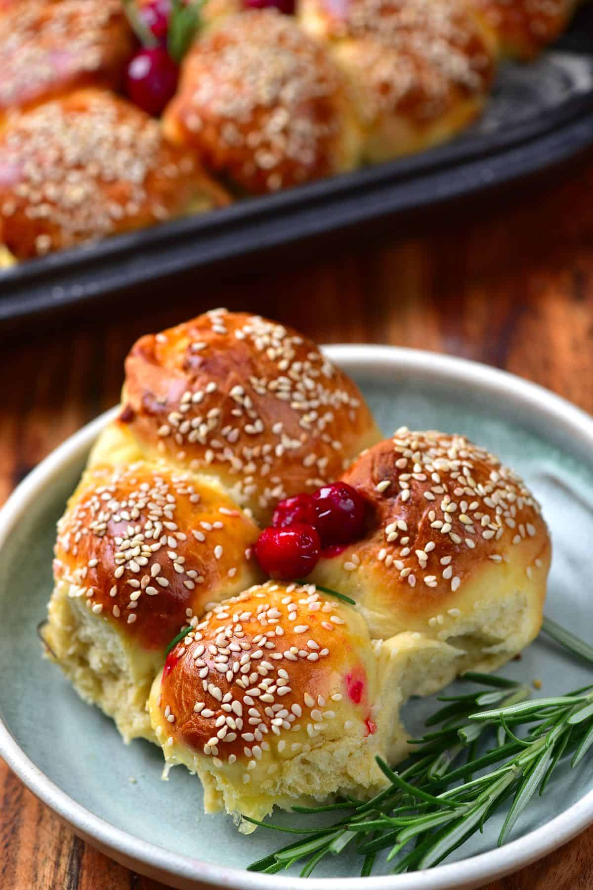 Four cheese buns in a plate with some rosemary and cranberries