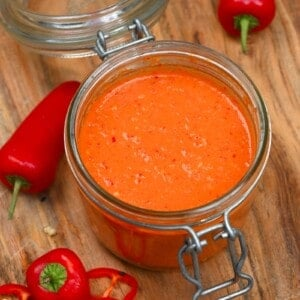 Red chili sauce in a jar wit some chilies around it