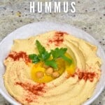 Hummus in a bowl topped with chickpeas and paprika