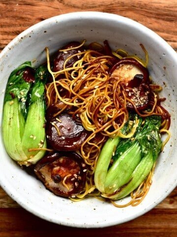 Dan dan noodles with bok choy and mushrooms in a bowl